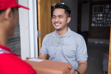 Photo for Smiling delivery man in red uniform delivering parcel box to recipient - Royalty Free Image