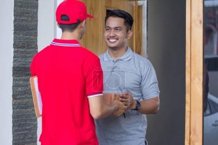 man in red uniform delivering parcel