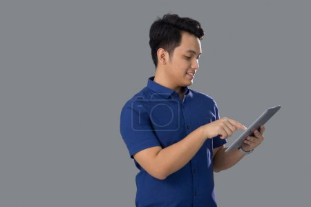 Asian Young Man in Casual using tablet