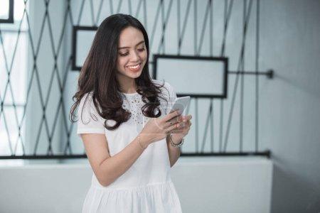 Pretty woman smiling using smart phone