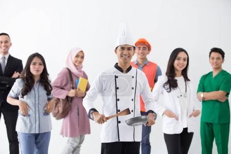 Photo pour Chef souriant debout en arrière-plan ensemble de profession diversifiée - image libre de droit