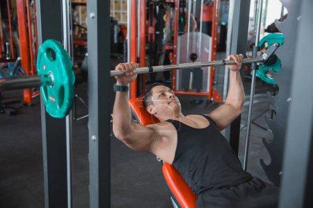 Muscular bodybuilder bench press workout with smith machine