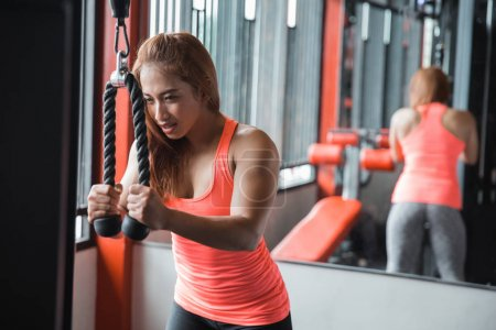 Young woman exercising triceps pushdown