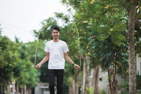 fit young man with jump rope in a park