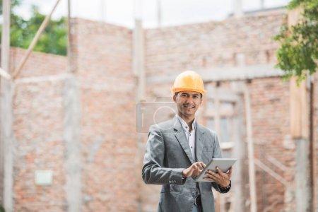 Foto de Hombre edificio diseñadores o arquitecto usar cascos con tablet pc frente a casa de ladrillo sin terminar - Imagen libre de derechos