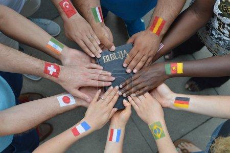 Photo pour Frères et sœurs internationaux dans le Christ avec différents drapeaux peints sur leurs bras tenant une bible ensemble - image libre de droit