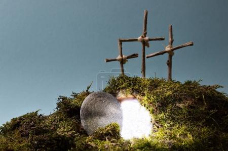 Photo pour Jardin de résurrection comme décoration de Pâques avec une pierre près du tombeau vide rempli de lumière aveuglante et trois croix sur une colline au-dessus - image libre de droit