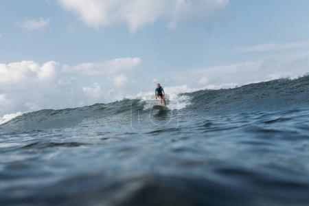 sportsman surfing wave on board in ocean