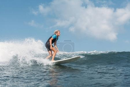 male surfer riding wave on surf board in ocean