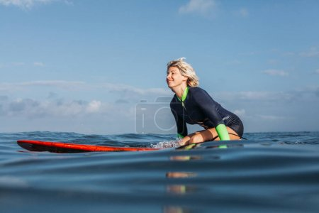 cheerful woman sitting on surf board in ocean