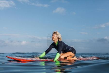 happy sportswoman sitting on surf board in ocean