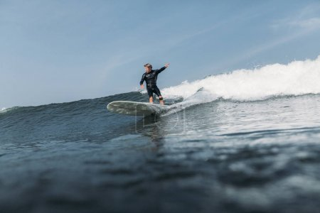 man having fun and surfing wave on board in ocean