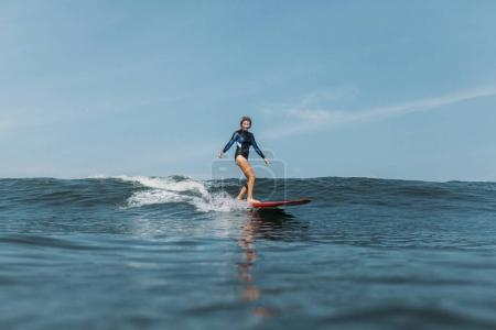 sportswoman having fun and riding wave on surf board in ocean
