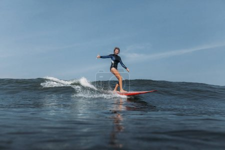 woman having fun and riding wave on surf board in ocean