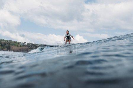 vague d'équitation femme sur planche de surf dans l'océan