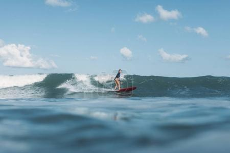 sportswoman riding wave on surf board in ocean