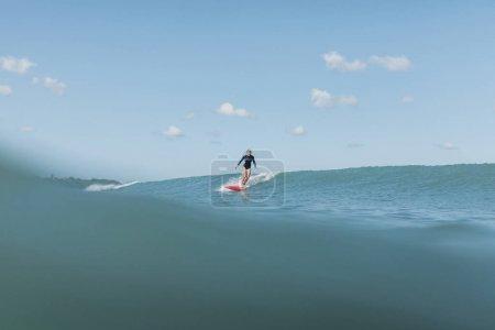 female surfer riding wave on surf board in ocean