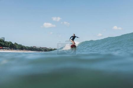 Photo pour Femme surfeuse chevauchant vague à bord dans l'océan - image libre de droit