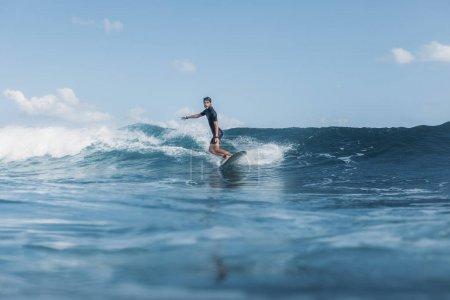 sportsman surfing wave on board in ocean