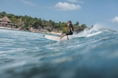 Photo for Male surfer riding wave on surf board in ocean - Royalty Free Image