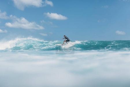 Foto de Onda de montar a caballo del hombre activo en tabla de surf en el océano - Imagen libre de derechos