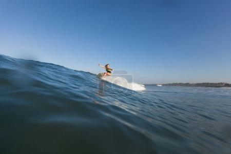 woman surfing the wave on surf board in ocean