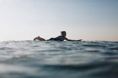 silhouette of woman lying on surf board in ocean