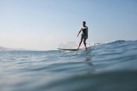 sportswoman standing on surf board in ocean