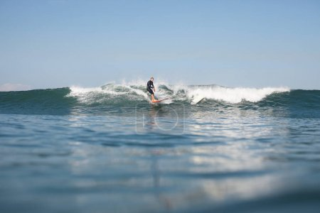 active man surfing wave on board in ocean