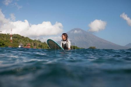 Photo pour Fille assise sur la planche de surf dans l'océan, le littoral en arrière-plan - image libre de droit