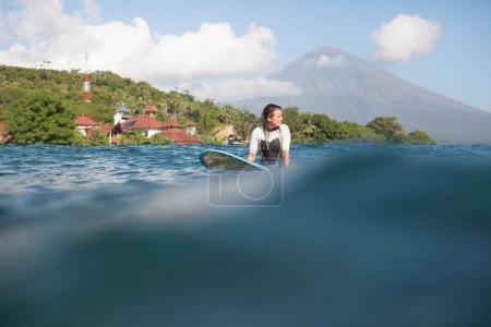 surfer sitting on surf board in ocean, coastline on background