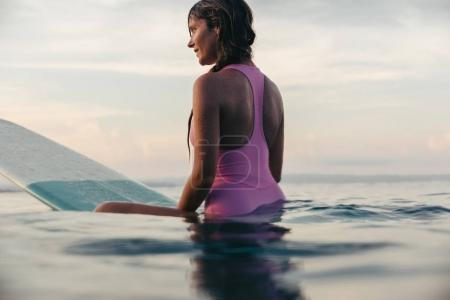 Photo for Beautiful woman sitting on surfboard in ocean at sunset - Royalty Free Image