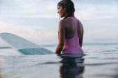 attractive woman sitting on surfboard in ocean at sunset