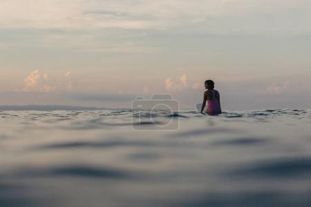 silhouette of surfer sitting on surfboard in water at sunset