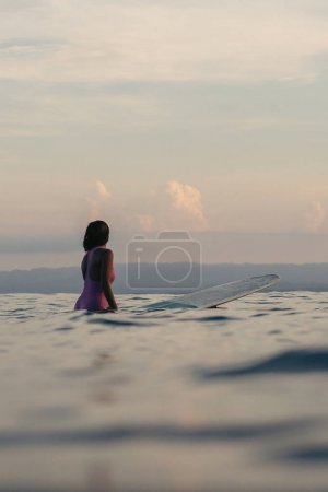 back view of female surfer sitting on surfboard in water at sunset