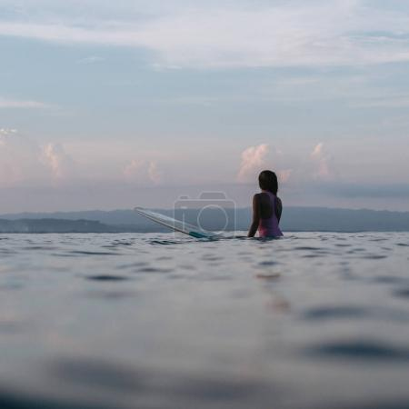 Photo for Silhouette of female surfer sitting on surfboard in ocean at sunset - Royalty Free Image