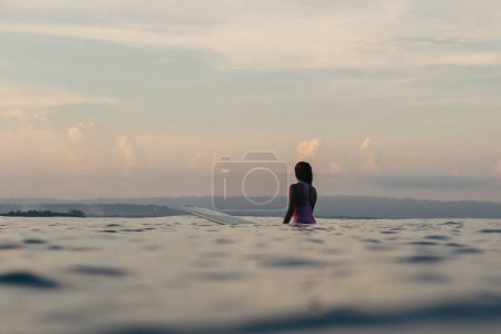 silhouette of surfer sitting on surfboard in sea at sunset