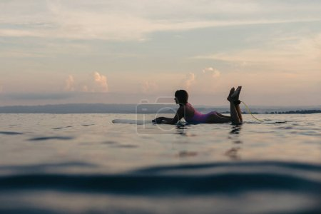 silhouette of girl lying on surfboard in water in ocean at sunset