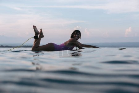 smiling woman lying on surfboard in water in ocean at sunset