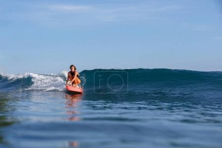 young female surfer riding wave on surfboard