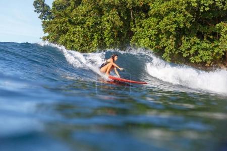 Photo pour Surfeur sportif équitation vague sur planche de surf dans l'océan - image libre de droit