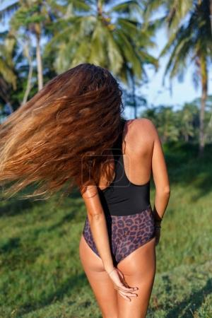 Photo for Rear view of girl with long hair on tropical resort - Royalty Free Image