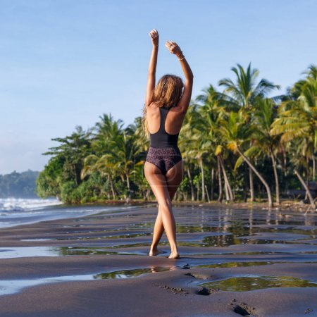 Photo for Back view of slim girl in swimsuit on tropical beach - Royalty Free Image