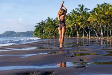 Photo for Rear view of slim girl in swimsuit posing on tropical beach - Royalty Free Image