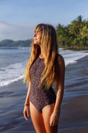Photo for Attractive tanned girl with long hair posing on tropical beach near ocean - Royalty Free Image