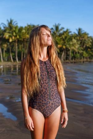 beautiful tanned girl with long hair posing on tropical beach