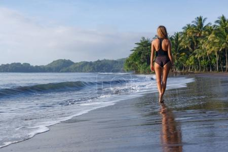 back view of young girl walking on tropical beach near ocean