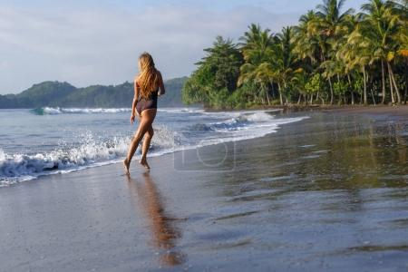 Photo for Rear view of girl running on tropical beach near ocean - Royalty Free Image