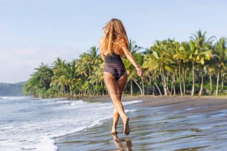 back view of young girl running on tropical beach near sea