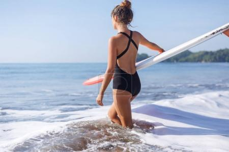 Photo for Young woman in black swimsuit holding surfboard and doing into water - Royalty Free Image